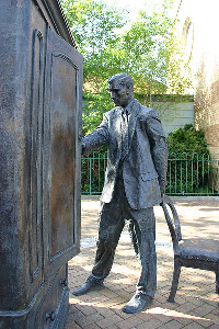 Statue of C.S. Lewis looking into a wardrobe.