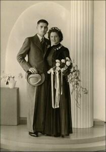 Trouwfoto van mijn ouders, 02-07-1942. Zij trouwden tijdens WO II, er was geen witte trouwjurk beschikbaar in die dagen, dus ze is getrouwd in het blauw! De blauwe trouwjurk was gemaakt van kant en zijde. De prijs van het bruiloftpak dat mijn vader draagt, was ongeveer 25 gulden, nogal een prijs in die tijd. De prijs van mijn moeders trouwjurk is niet bekend, haar moeder heeft de rekening betaald. Foto gemaakt door studio Hameter, Voorstraat 291 in Dordrecht